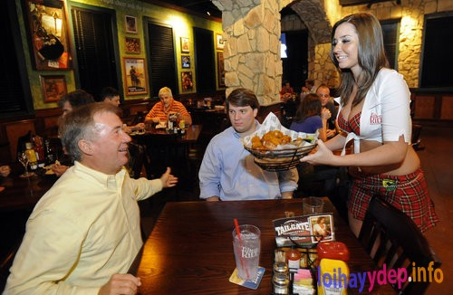 091003 Kennesaw - Elizabeth Allen (right) serves hot wings to Marty Flowler (left), of Kennesaw, as his son Marty Fowler Jr. looks on at Tilted Kilt Pub & Eatery in Kennesaw. The Tilted Kilt, an Irish-themed chain, opens this week its third metro-Atlanta location in Kennesaw and in less than three months. Saturday, October 3, 2009. Hyosub Shin, hshin@ajc.com